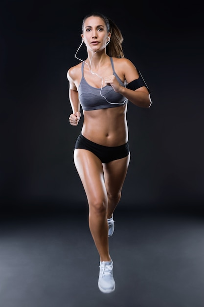 Fit and sporty young woman running over black background 1301 7568