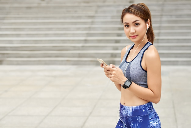 Fit asian woman in sportswear, with earphones and smartphone posing in street Free Photo