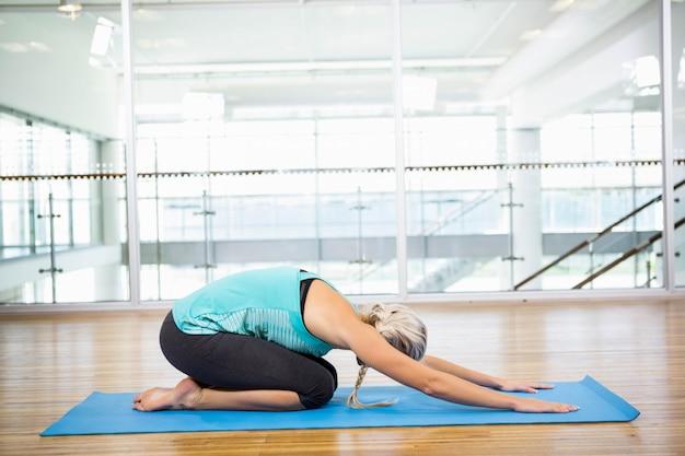 Fit blonde doing yoga on mat in the studio Premium Photo
