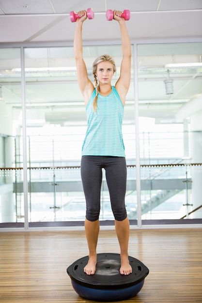 Fit blonde standing on bosu ball and lifting dumbbells in fitness studio Premium Photo