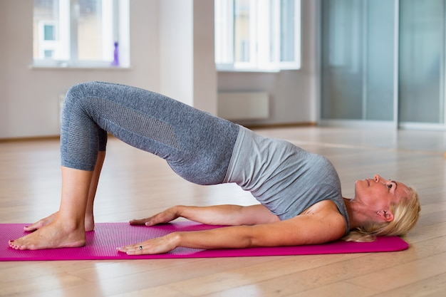 Fit blonde woman practicing yoga Free Photo