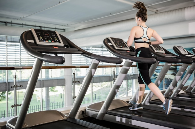 Fit brunette running on treadmill at the gym Premium Photo