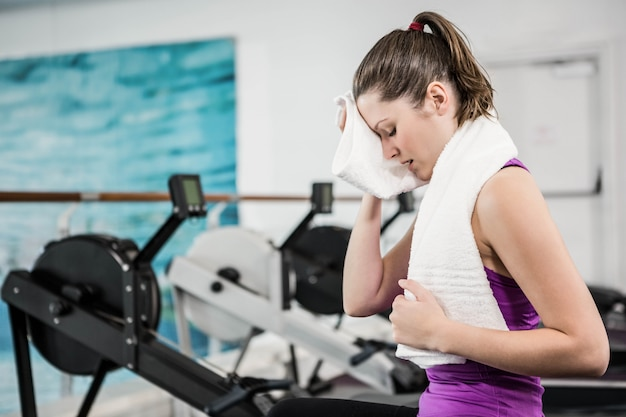 Fit brunette wiping sweat with towel at the gym Premium Photo