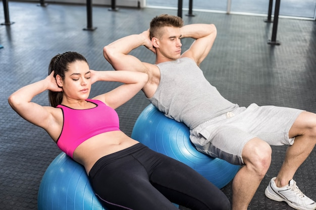 Fit couple doing abdominal crunches on fitness ball at gym Premium Photo