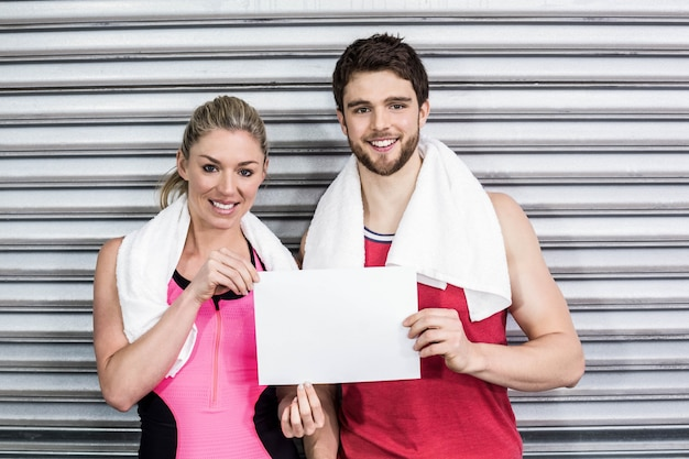 Fit couple holding blank paper at crossfit gym Premium Photo