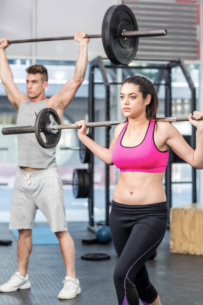 Fit couple lifting barbell at gym Premium Photo