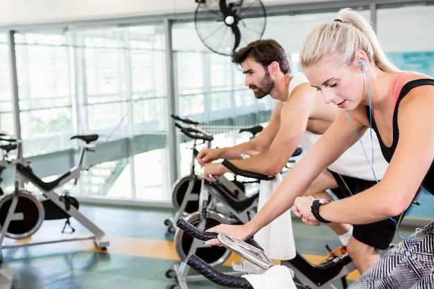 Fit couple using exercise bikes at the gym Premium Photo
