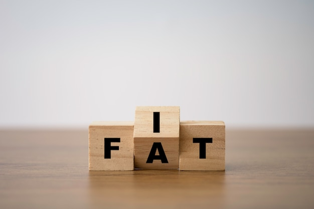 Fit and fat wording print screen on wooden cube block. diet and good health condition. Premium Photo