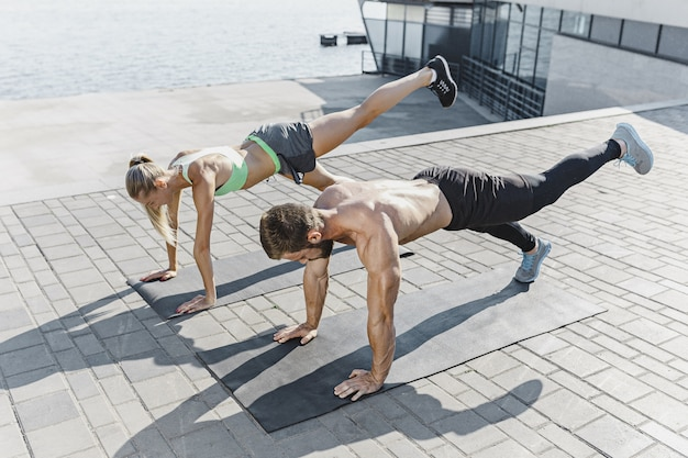 Fit fitness woman and man doing fitness exercises outdoors at city Free Photo