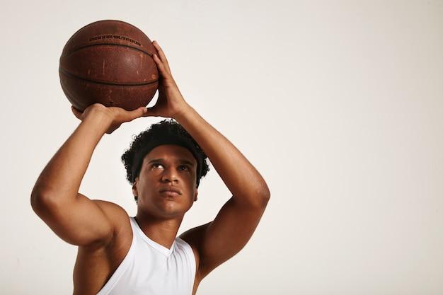 Fit giocatore afroamericano concentrato con un corto afro in camicia bianca senza maniche si prepara a lanciare un vecchio pallone da basket in pelle Foto Gratuite