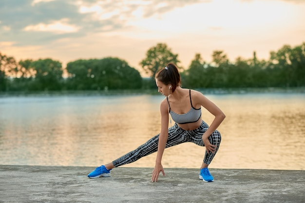 Fit girl doing fitness exercises outside in the evening. wearing stylish modern sportwear. Premium Photo