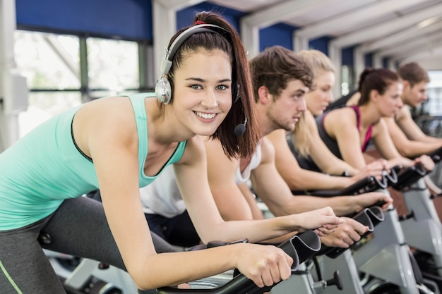 Fit group of people using exercise bike together in gym Premium Photo
