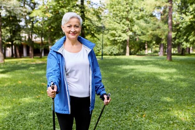Montare una donna matura dai capelli grigi felice in abbigliamento sportivo che gode di attività fisica che promuove la salute utilizzando bastoncini da passeggio con un'espressione facciale gioiosa eccitata, respirando aria fresca nella natura selvaggia, sorridente Foto Gratuite