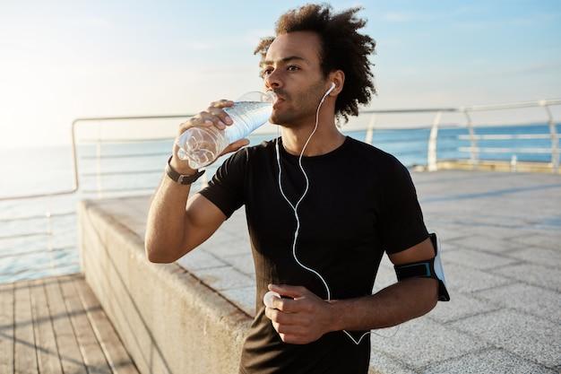 午前中に洋ナシでジョギングした後、ペットボトルから男性アスリート飲料水をフィットさせます 無料写真