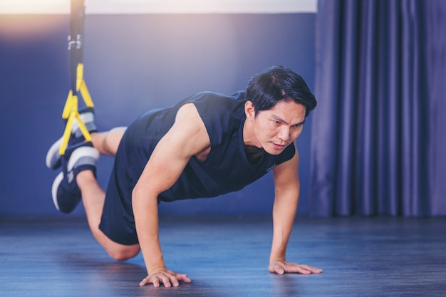 Fit man doing plank exercise for back spine by push ups with rope fitness straps in the gym Premium Photo