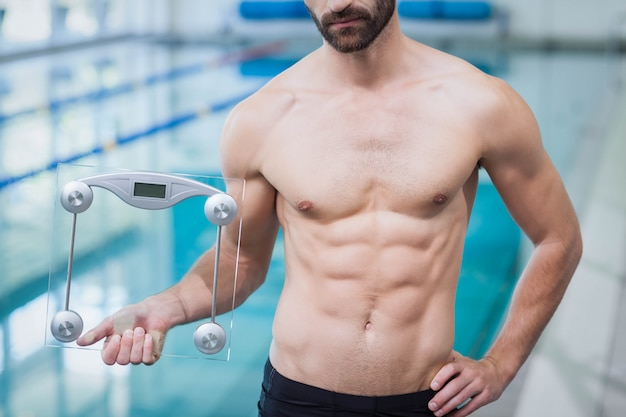 Fit man holding a weighting scale at the pool Premium Photo