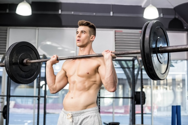 Fit man lifting barbell at gym Premium Photo