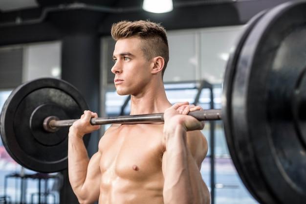 Fit man lifting barbell at gym Premium Photo