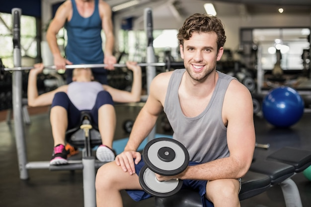 Fit man lifting dumbbell at gym Premium Photo