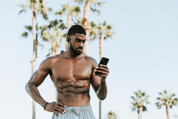 Fit man listening to music while at the beach Premium Photo