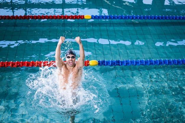 Fit man triumphing in the pool Premium Photo