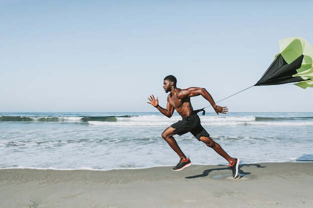 Fit man with a running parachute at the beach Premium Photo