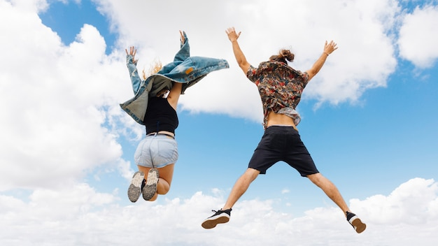 Fit man and woman jump for joy Free Photo