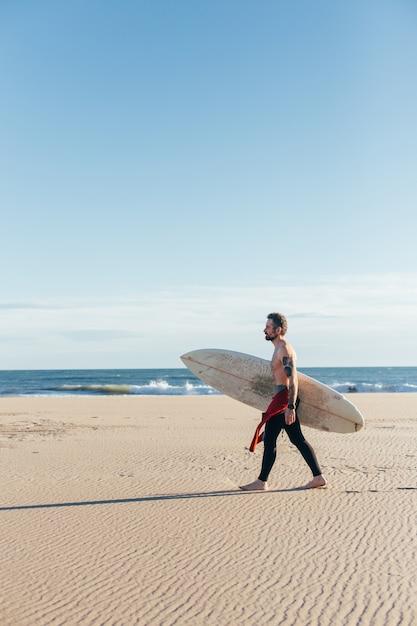 暖かい夏の日に空のビーチでサーフボードと中年の男性をフィットさせます 無料写真