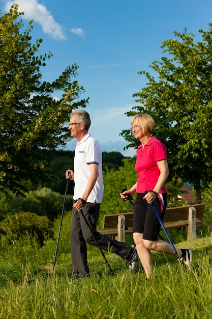 Fit senior couple with nordic walking sticks enjoying their hike in the nature Premium Photo