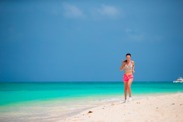 Fit sports young woman running along tropical beach in her sportswear Premium Photo