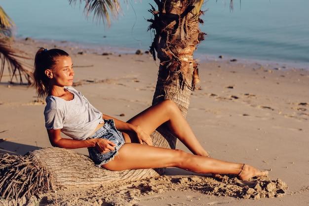 해질녘 열대 해변에서 상단과 반바지에 검게 그을린 슬림 여성을 맞추십시오. 무료 사진