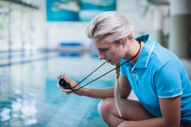 Fit trainer showing stopwatch at the pool Premium Photo