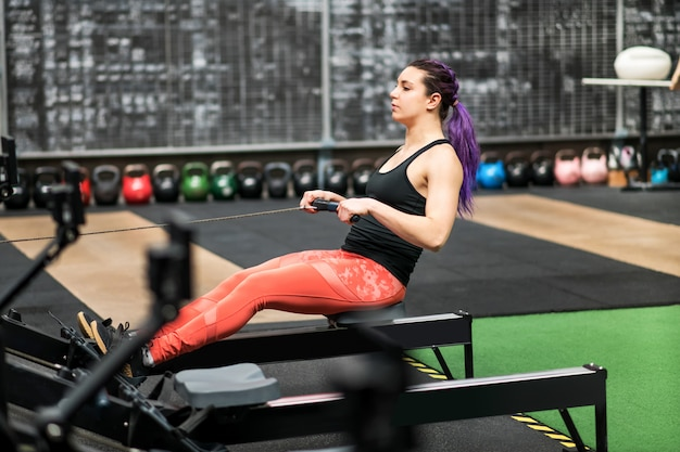 Fit woman athlete working out on a rowing machine Premium Photo