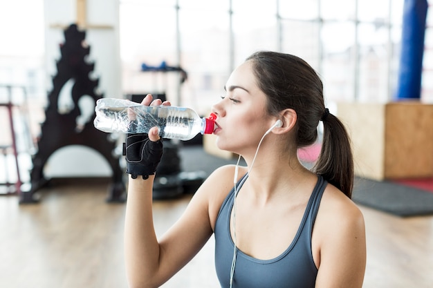 Fit woman in headphones drinking Free Photo