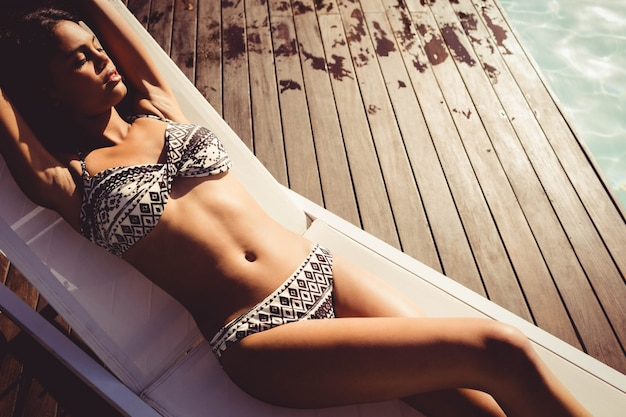 Fit woman lying on deck chair by the pool | Premium Photo