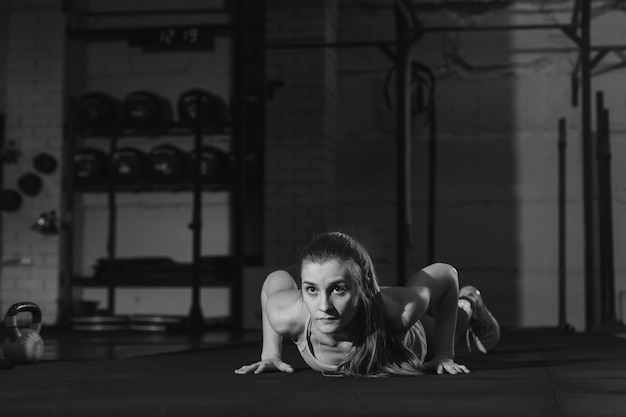 Fit woman in pink colourful sportswear doing burpees on a purple exercise mat in a grungy industrial type space Premium Photo