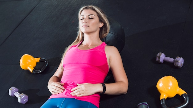 Fit woman resting on floor near exercise equipments Free Photo
