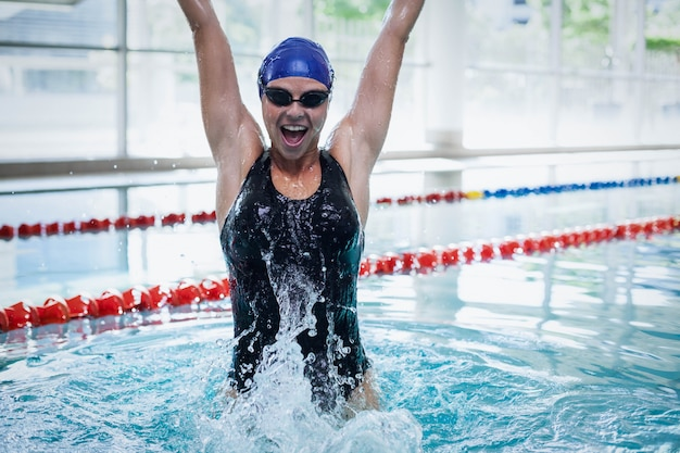Fit woman triumphing with raised arms at the pool Premium Photo