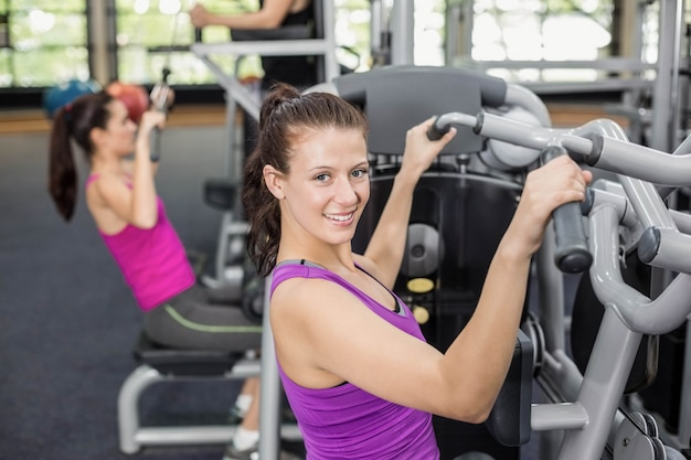 Fit woman using weight machine in gym Premium Photo
