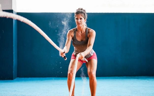Подходит женщина с боевой веревкой в тренажерном зале Premium Фотографии