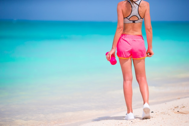 Fit young girl with bottle of water on white beach Premium Photo