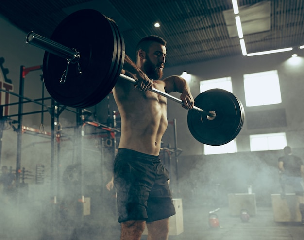 Fit young man lifting barbells working out in a gym Free Photo
