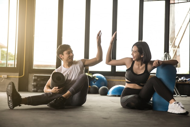 Fit young man and woman exercising in gym Premium Photo