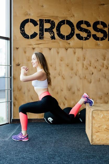 Подходящая коробка молодой женщины прыгает в спортзале стиля crossfit. спортсменка выполняет прыжки на ящик в тренажерном зале. Бесплатные Фотографии