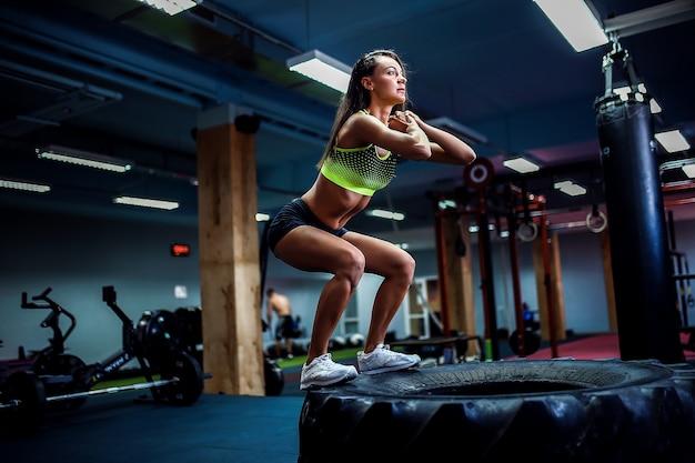 Подходит молодая женщина, прыгает в стиле кроссфит Premium Фотографии