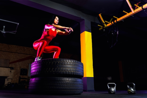 Подходящая молодая женщина прыгает на шинах Premium Фотографии
