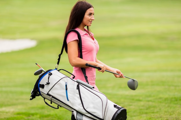 Fit young woman carrying golf clubs Free Photo