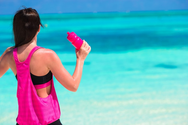 Fit young woman drink water on white beach Premium Photo