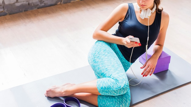 Fit young woman sitting on exercise mat using cellphone Free Photo