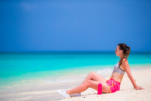 Fit young woman on tropical white beach in her sportswear Premium Photo
